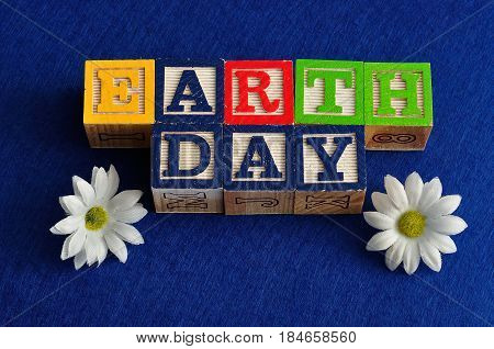 Earth day spelled with colorful alphabet blocks isolated on a blue background and white daisies