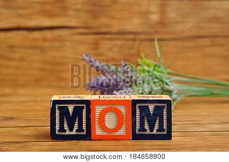 Mom spelled with colorful alphabet blocks and lavender in the background