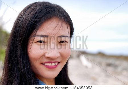A smiling chinese woman outside on an overcast day on Silver Sands State Park in Milford Connecticut.