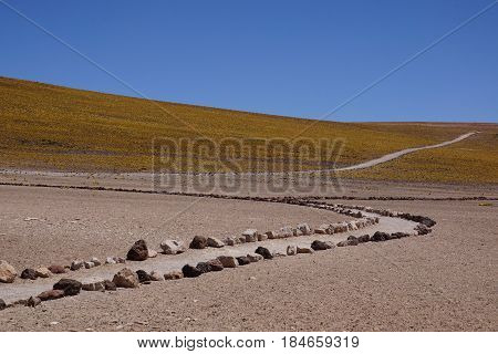 A desert trail lined by rocks leading up a Hill in the Middle of Nowhere