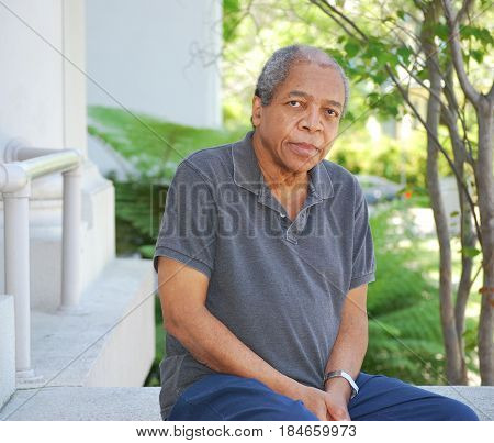 African american male sitting on steps outside.