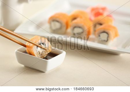 Dipping tasty roll into bowl with soy sauce on table