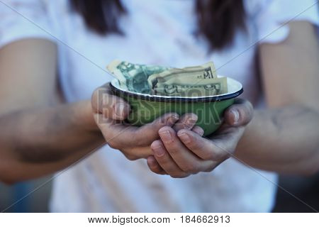 Poor woman holding bowl with money