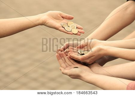 Woman sharing money with poor people