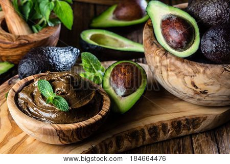 Raw avocado chocolate mousse pudding with mint in olive wooden bowl. Vegan vegetarian food. Organic healthy dessert. Close up