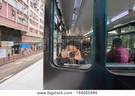 HONG KONG - CIRCA DECEMBER, 2015: boy taking photo from a tram. Hong Kong Tramways is one of the earliest forms of public transport in the metropolis.