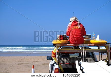 Newquay, Cornwall, Uk - August 7 2017: Female Rnli Lifeguard Keeping Watch On Top Of A Truck On A Su