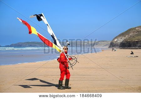 Newquay, Cornwall, Uk - August 7 2017: Female Rnli Lifeguard Moving The Beach Warning Swim And Surf