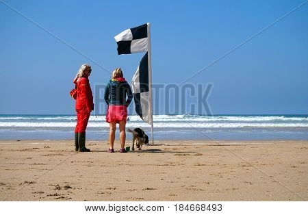 Newquay, Cornwall, Uk - August 7 2017: Female Rnli Lifeguard Talking To A Woman With A Dog Near A Be