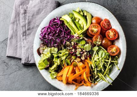 Vegan buddha bowl. Bowl with fresh raw vegetables - cabbage, carrot, zucchini, lettuce, watercress salad, tomatoes cherry and avocado, nuts and pomegranate. Slate background. Top view