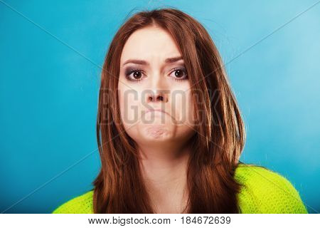 Young people teenage concept - teen funny girl making silly face unhappy face expression on blue