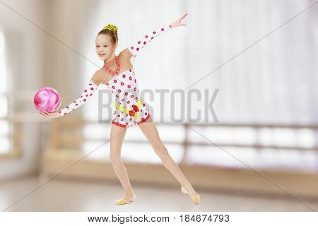 Beautiful little girl gymnast dressed in sports suits for competition, performs exercises with the ball.In the sports hall with mirror and a large semi-circular window.