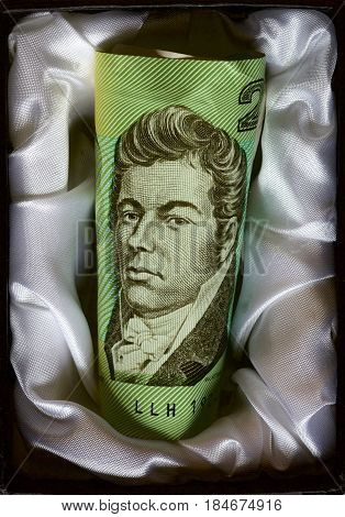 Discontinued Australian two dollar note resting in a casket.