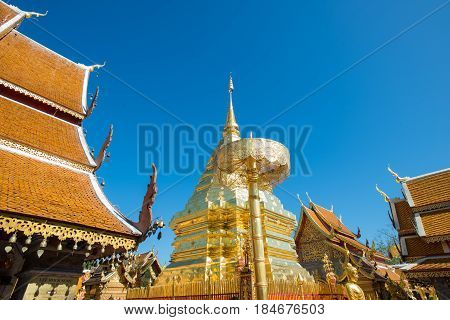 Gold Pagoda And Gold Buddha Statue With Blue Sky At Wat Phra That Doi Suthep, Chiang Mai, Thailand.
