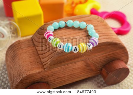 Bracelet with baby name Noah on wooden toy car