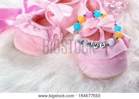 Bracelet with baby name Emma and booties on white fluffy background