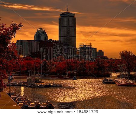 A beautiful sunset with a bright yellow and orange sky surrounded by autumn trees and water with boats.