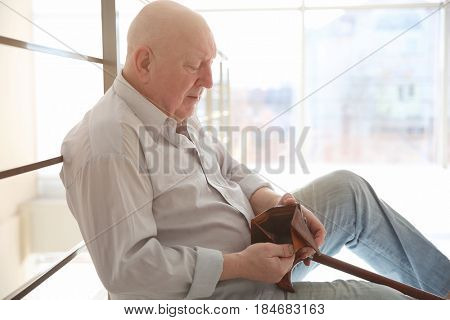 Senior man sitting near banisters with empty purse. Poverty concept