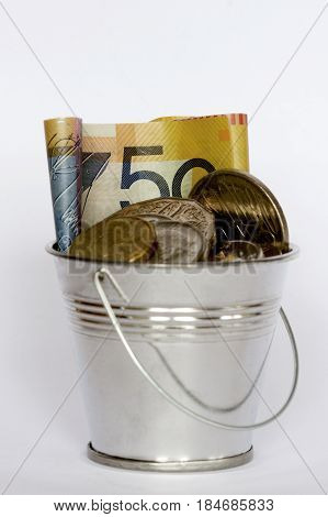 A bucket full of Australian money: fifty dollar note and coins.
