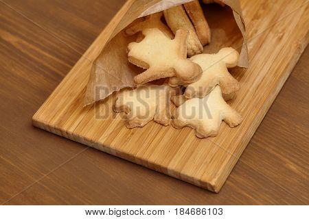 Baking gingerbread man cookies on wooden board closeup