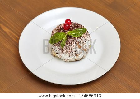 Round pastry ball cake covered with white cream and mint on wooden table