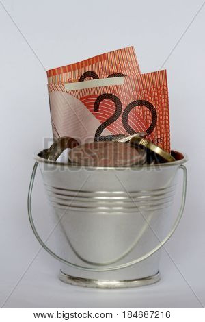 A bucket full of Australian money: twenty dollar note and coins.