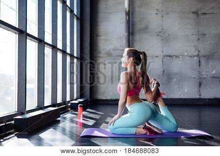 Yoga Mat Woman Stretching Hip, Hamstring Muscles, Leg Muscles With Pigeon Pose Stretch.