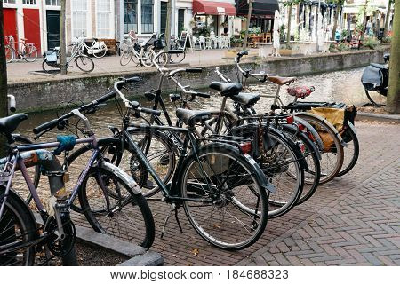 Delft Netherlands - August 3 2016: Picturesque street in the dutch city of Delft with bicycles parked along the canal