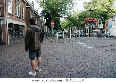 Delft Netherlands - August 3 2016: Tourist in picturesque street in the dutch city of Delft