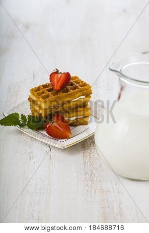 Delicious Waffle With Berries And  Jug Of Milk On Wooden Table.