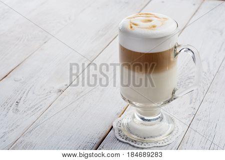latte macchiato coffee on white wooden background.