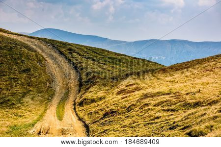 summer mountain landscape. path through the hill to the top. mountain ridge is seen in the distance