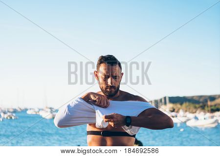 Adult fit sportsman with HRM device on chest putting on white t-shirt.