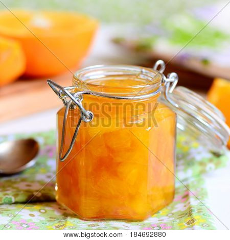 Tasty jam made from oranges. Home fruit jam in a glass jar, textile napkin, orange slices on a table. Useful citrus dessert recipe. Closeup