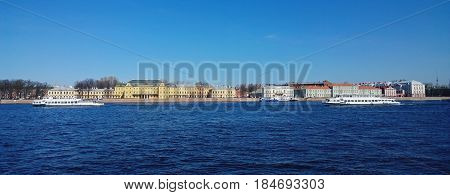 Panoramic view of St. Petersburg: Universitetskaya embankment with the Menshikov Palace and three boats on the Neva river in Sunny day