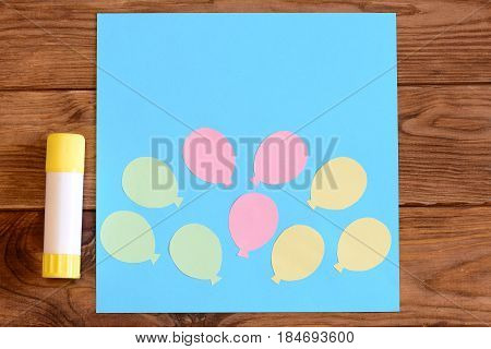 Making a card with paper air balloons. Step. Tutorial for kids. Card with paper air balloons, glue stick on a wooden table. Preschool paper and glue crafts activities. Closeup. Top view