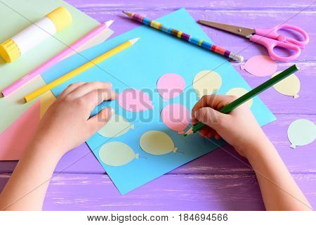 Small child doing a paper card. Child holds a pencil in hand. Card with paper air balloons, scissors, glue stick, colored paper, pencils on a table. Simple preschool and kindergarten craft projects