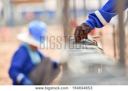 Construction workers hands using steel wire construction and pincers to secure rebar before concrete is poured over it in construction sit mega construction projectConstruction concept