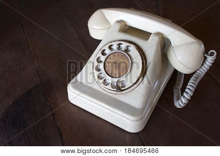 Old white phone with dust circle dialpad and scratches on wooden retro desk. Vintage desk telephone concept.