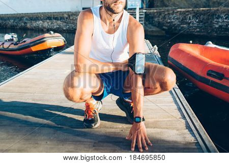 Horizontal outdoors shot of man with armband and headphones sitting on pier.