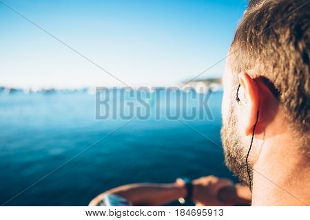 Back view of a man listening to music and admiring the seascape.
