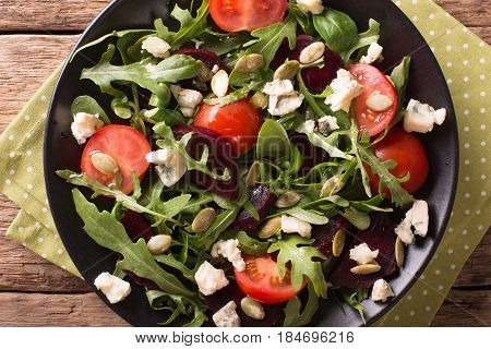 Salad With Beets, Arugula, Tomatoes, Roquefort Cheese And Pumpkin Seeds Close-up. Horizontal Top Vie