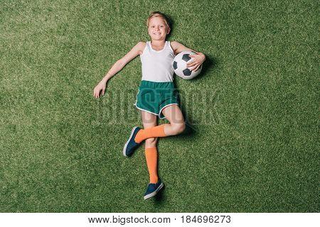 Top View Of Little Boy Holding Soccer Ball On Grass, Athletics Children Concept