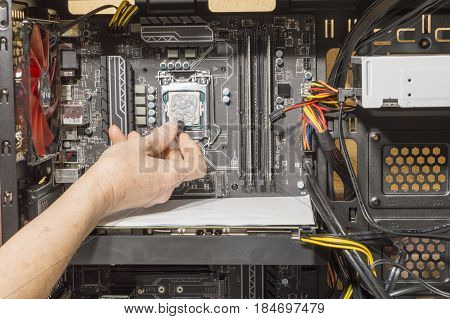 A person applies thermal grease to the computer microprocessor