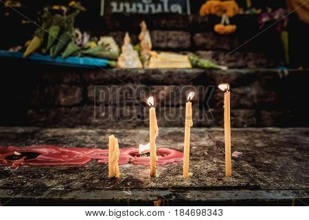 lot of candle lighted from faith of people inside a Buddhist temple. vintage effect.