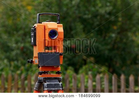 the orange theodolite is mounting on a tripod