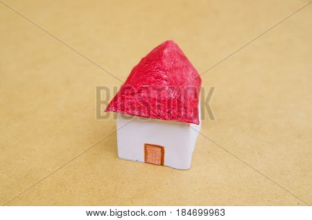 A small beautiful house made of paper with a red roof, real estate in a model concept.