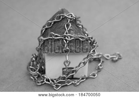 Chain wrapped around a beautiful an small model house made of paper in black and white.