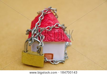 House in chains locked with padlock, mortgage and foreclosure concept.