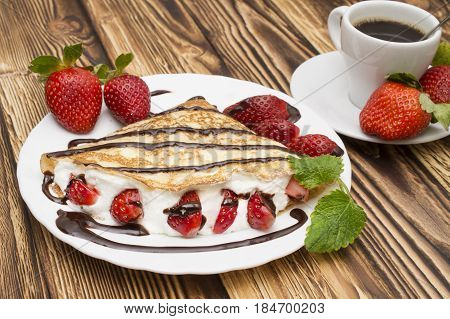 Crepes with Banana, Chocolate and strawberries on a wooden background, pancakes